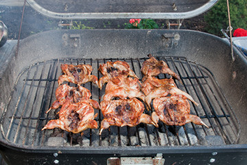 BBQ quails cooking on a grill in the garden