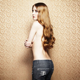Fashion photo of the young sensual woman in jeans