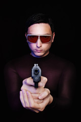 criminal pointing a gun in sunglasses in the dark