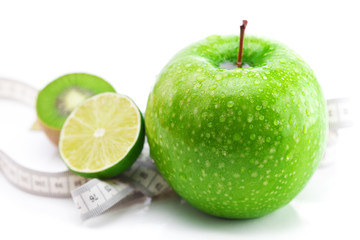 lime,apple with water drops,kiwi and measure tape isolated on wh