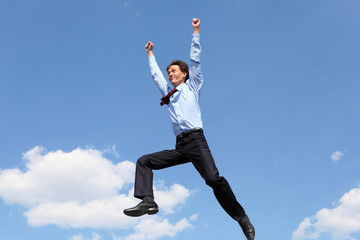 jumping young businessman in a blue shirt