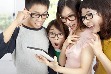 young group using tablet pc and surprised