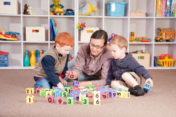 Boys playing game with kids blocks with mother