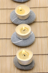 Row of candles and stones on bamboo stick straw mat