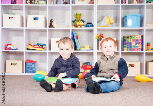 Smiling children reading kids books in play room
