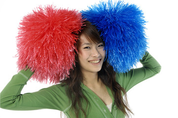 Young cheerleader with red and blue pom-poms smiling