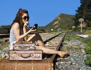 Young traveling woman with her suitcases on the railway tracks
