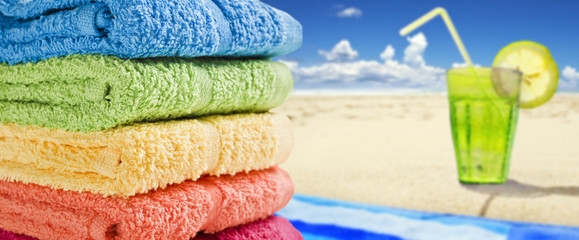 Colorful towels on a white with a cold drink