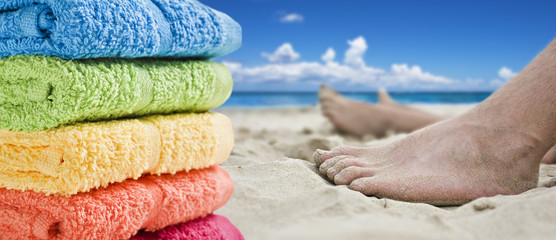 Colorful towels and bare feet on the beach