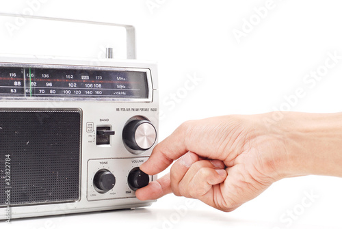 Hand Turning Up the Volume on Vintage AM FM Radio