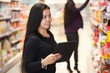Woman using digital tablet in shopping centre