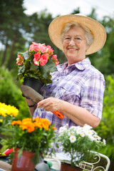 Senior woman with a pot of flowers in her garden