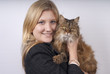 Blonde woman in black jacket holding brown tabby cat