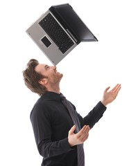 Happy man balancing a laptop on his nose