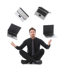 Businessman juggling with laptops