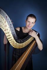 Frau lehnt sich auf Schulter einer Harfe