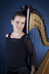 Frau steht vor Harfe
