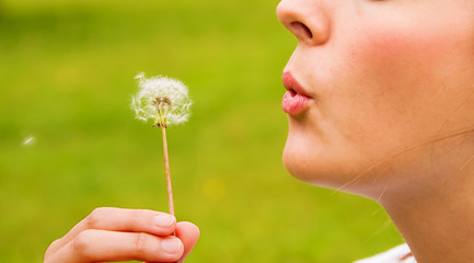 Young woman blowing a dandelion in springtime