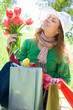 Beautiful woman with shopping bags and tulips
