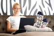 Beautiful young lady sitting on sofa, using laptop