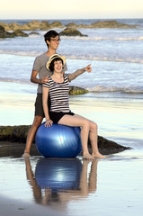 Young couple with fitness ball on beach