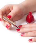 Manicurist applying red nail polish on female fingers poster