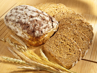 Freshly baked bread and wheat on table