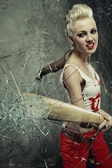 Punk girl broking a glass with a bat