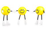 Three smiling toy little men on a white background