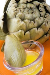 Steamed artichoke with melted butter on an orange ceramic plate