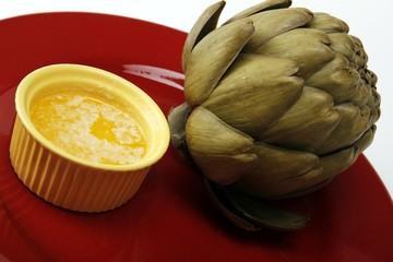 Steamed artichoke with melted butter on a red ceramic plate