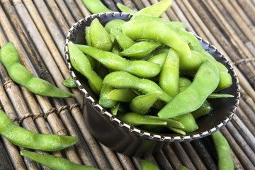 Edamame soy beans in a brown ceramic dish