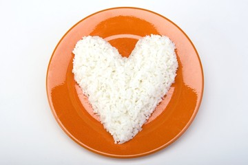 Heart shaped white rice on a ceramic plate