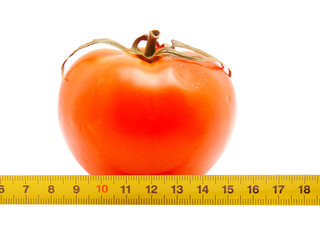 Tomato and ruler on a white background