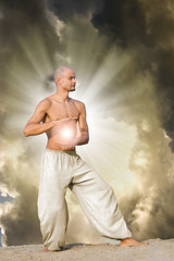 Man Practises Tai holding a Ball of Energy with Dramatic Cloudy