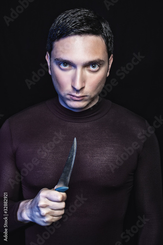 Young man in black with kitchen knife ready to stab