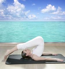black mat yoga woman window turquoise sea view