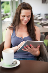 Young woman using her tablet in a cafe