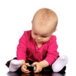 Infant baby girl playing with a t.v. remote