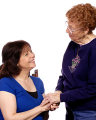 An older woman greeting a younger woman with a hand shake