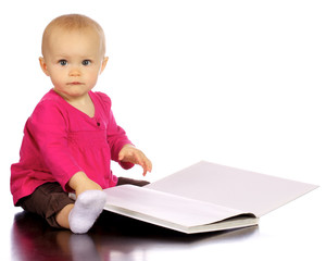 Infant baby girl enjoying and discovering books