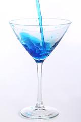 Blue liquid pouring into glass