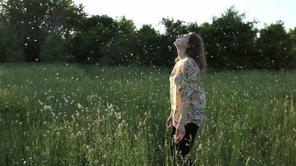 girl plays with dandelions in the meadow