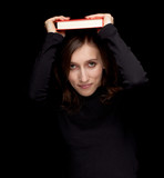 young woman with book on head, black background
