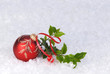 red christmas ornament with holly and ribbon on a bed of snow