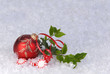 red christmas ornament with holly , ribbon, and candy on snow