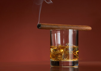 Whiskey with ice cubes and cigar, on brown
