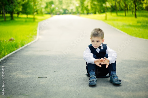 boy sitting down in a park
