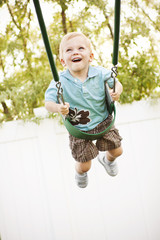 Cute little boy smiling on a swing