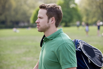 A young man walking through a park, carrying a sports bag